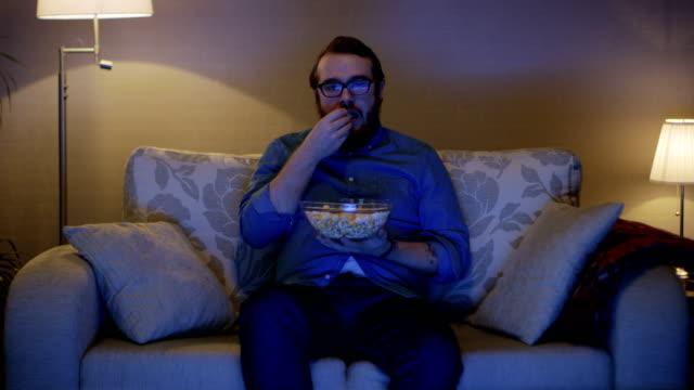 stockvideo's en b-roll-footage met portret shot van een man zittend op een sofa in zijn woonkamer, het eten van popcorn en tv kijken. vloerlampen zijn ingeschakeld. - popcorn