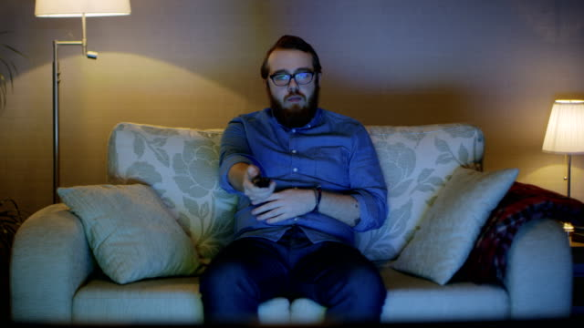portrait shot of a man sitting on a sofa in his living room, watching tv, changing channels. floor lamps are turned on. - guy sofa video stock e b–roll