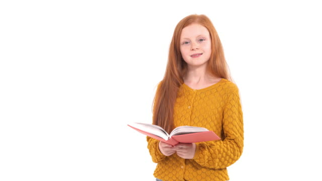 Portrait shot of a school girl with long foxy hair holding and reading a book. Educational concept. Isolated, on white background
