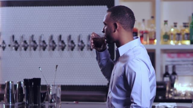 vídeos de stock, filmes e b-roll de tiro do retrato de um homem afro-americano atraente jovem olhando para a câmera e consumir bebida alcoólica em um bar - costumer