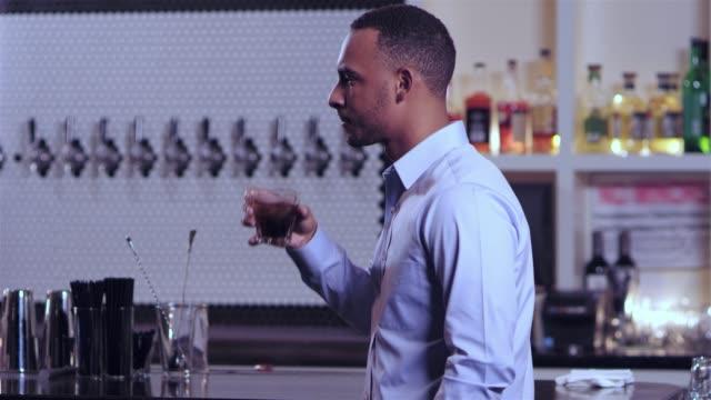 vídeos de stock, filmes e b-roll de tiro do retrato de um homem afro-americano atraente jovem olhando para a câmera de forma seious num bar - costumer