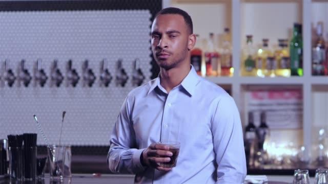 vídeos de stock, filmes e b-roll de tiro do retrato de um homem afro-americano atraente jovem balançando a cabeça em dissaproval, ao consumir bebida alcoólica em um bar - costumer