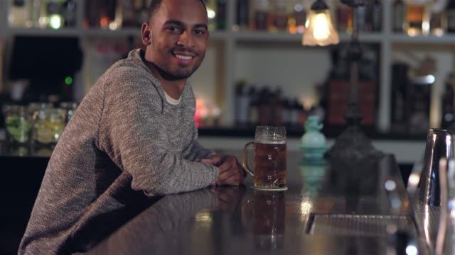 vídeos de stock, filmes e b-roll de tiro do retrato de um homem afro-americano atraente jovem sorrindo e tomar um gole de sua cerveja num bar - costumer