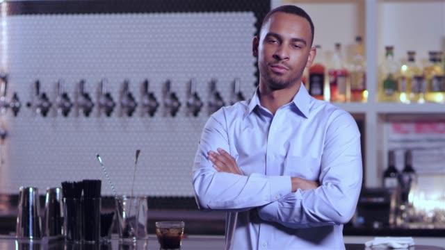 vídeos de stock, filmes e b-roll de tiro do retrato de um homem afro-americano atraente jovem sorrindo com seus braços cruzados em um bar - costumer