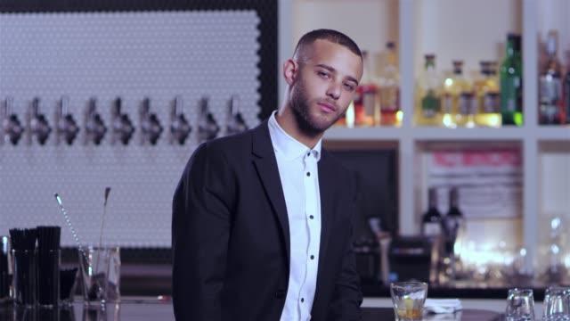 vídeos de stock, filmes e b-roll de tiro do retrato de um homem afro-americano atraente jovem olhando fixamente para a câmera em um bar - costumer