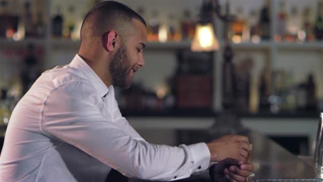 vídeos de stock, filmes e b-roll de tiro do retrato de um homem afro-americano atraente jovem tomar um gole de sua bebida alcoólica e sorrindo para a câmera, um bar - costumer