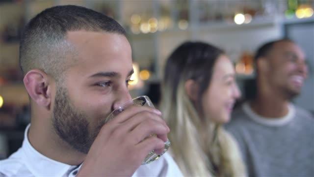 vídeos de stock, filmes e b-roll de tiro do retrato de um jovem afro-americano homem atraente tomar um gole de sua bebida, sorrindo e rindo de um bar. seus amigos conversando e rindo no fundo - costumer
