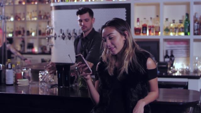 vídeos de stock, filmes e b-roll de tiro de retrato de uma jovem mulher asiática atraente olhando para o celular num bar - costumer