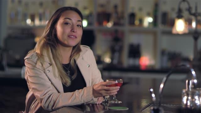 vídeos de stock, filmes e b-roll de tiro de retrato de uma jovem mulher asiática atraente sorrir e beber a sua bebida alcoólica em um bar - costumer