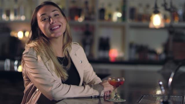 vídeos de stock, filmes e b-roll de tiro de retrato de uma jovem mulher asiática atraente sorrindo para a câmera em um bar - costumer