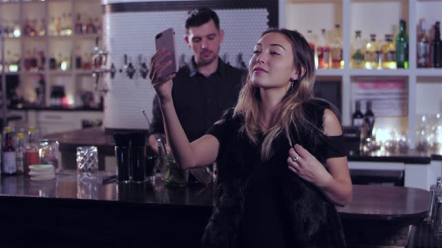 vídeos de stock, filmes e b-roll de tiro de retrato de uma jovem mulher asiática atraente tomando uma selfie num bar. então, ela passa a olhar para o celular dela - costumer