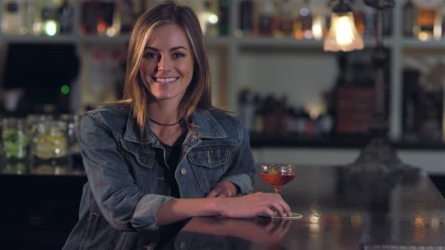 vídeos de stock, filmes e b-roll de tiro de retrato de uma jovem mulher loira atraente sorrir e tomar um gole de sua bebida alcoólica em um bar - costumer
