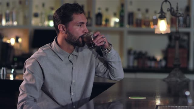 vídeos de stock, filmes e b-roll de tiro de retrato de um jovem atraente tomar um gole de sua bebida alcoólica e olhando uma câmera em um bar - costumer