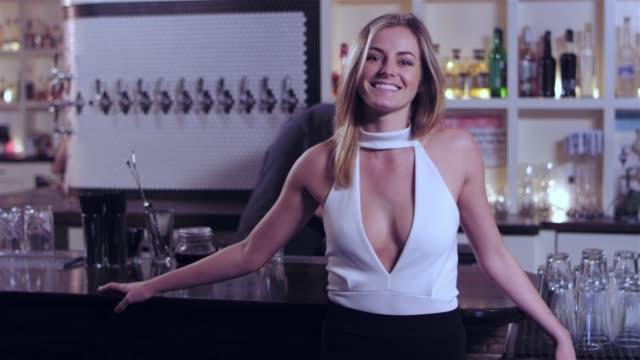 vídeos de stock, filmes e b-roll de tiro de retrato de uma jovem mulher atraente branca, sorrindo para a câmera, enquanto ela inclina-se em um bar - costumer