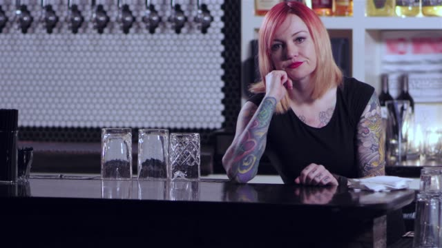 portrait shot of an attractive tattooed bartender lady looking really bored, and observing her watch at a bar - нетерпеливый стоковые видео и кадры b-roll