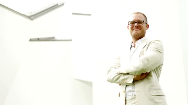 Portrait Shot of Successful Business Man in White Suit. White Buildings in the Background. video