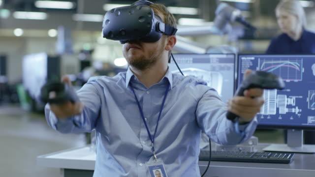 endüstri mühendisi giyen sanal gerçeklik kulaklık ve denetleyicileri, çalışmaya hazır kullanarak portre vurdu. arka planda üretim tesisi ve monitörler. - sanal gerçeklik stok videoları ve detay görüntü çekimi