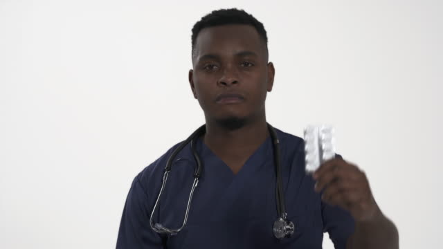 Portrait shot of young African doctor demonstrating blister packs with different types of pills. Healthcare and pharmacy. Choice concept