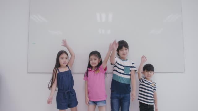 portret: uśmiechnięta grupa uczniów małych dzieci machnęła rękami edukacja stojąc przed klasą wiedzy edukacyjnej, zróżnicowane dzieci w szkole podstawowej - uniform filmów i materiałów b-roll