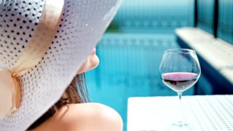 vidéos et rushes de portrait souriant jolie femme en disquette chapeau et des lunettes de soleil profiter de bains de soleil avec la coupe de vin - chapeau