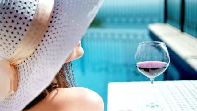 portrait smiling pretty woman in floppy hat and sunglasses enjoying sunbathing with goblet of wine - cappello video stock e b–roll