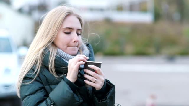 肖像微笑的年輕女子捧著一杯茶或咖啡, 在戶外喝酒, 在街上看著鏡頭在秋天 - {{asset.href}} 個影片檔及 b 捲影像
