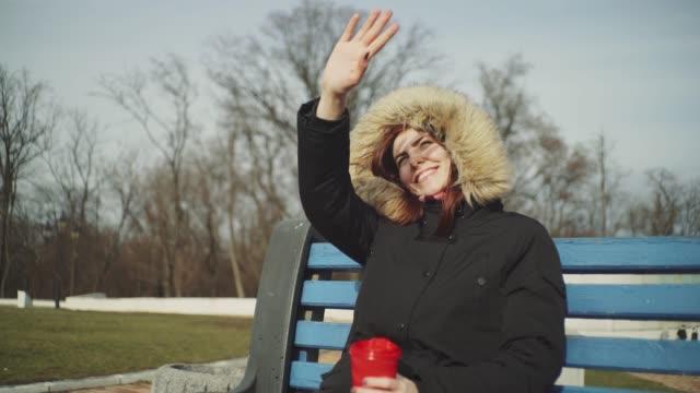 肖像微笑的年輕女子拿著一杯茶或咖啡和喝酒。在寒冷的陽光明媚的日子戶外 - {{asset.href}} 個影片檔及 b 捲影像