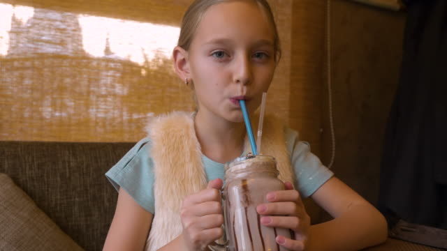 portrait teenager girl drinking milk shake cocktail at table in cafe close up - paglia video stock e b–roll