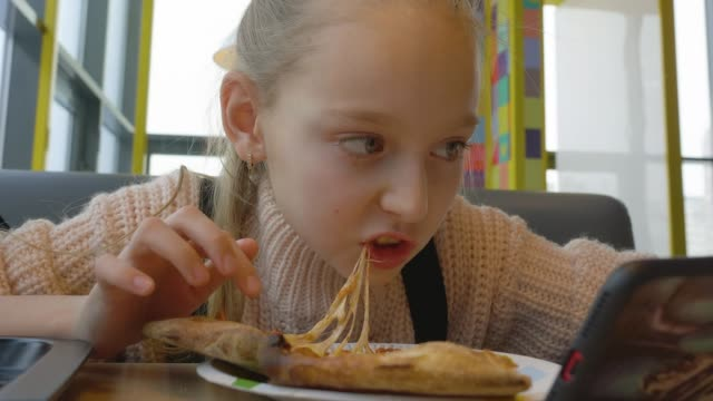 Portrait teenager girl eating cheesy pizza with salami in italian fast food cafe