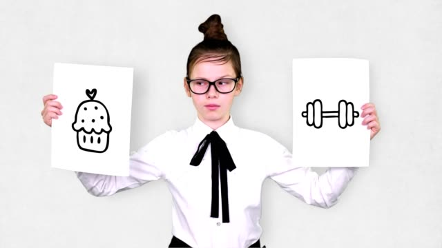 portrait, teenager girl holds two white paper sheets with cake and dumbbell drawings, animations. choice between sports and sweets, concept of healthy lifestyle choice