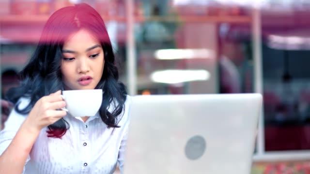 vídeos de stock e filmes b-roll de portrait thoughtful asian young woman enjoying having good time using laptop pc looking at screen - coffe shop