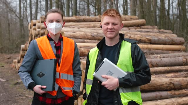 Portrait two logging workers. Face mask, tablet in hand. Focus attention camera.