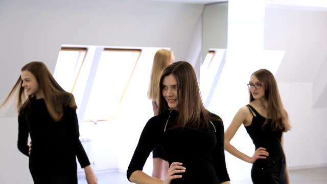 Portrait view of women posing in turn in model school video