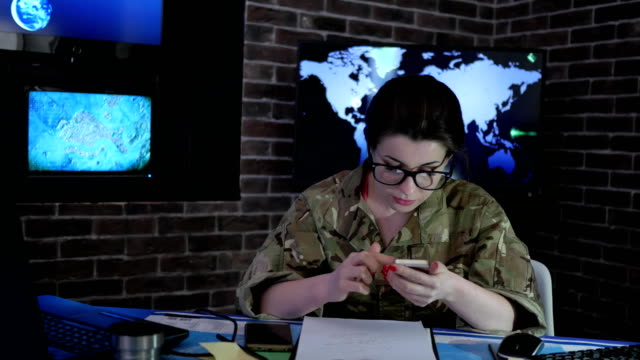 portrait woman soldier with mobile phone, control center, war video