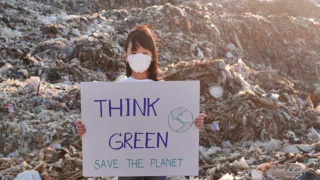 vídeos de stock, filmes e b-roll de retrato de uma garotinha asiática em um enorme depósito de lixo de aterro sumário na ásia e segurando cartazes para ativistas do movimento ambientalista que lutam pela natureza. voluntariado,caridade,limpeza,pessoas,conceito infantil,ecologia,crianças - ambiente evento