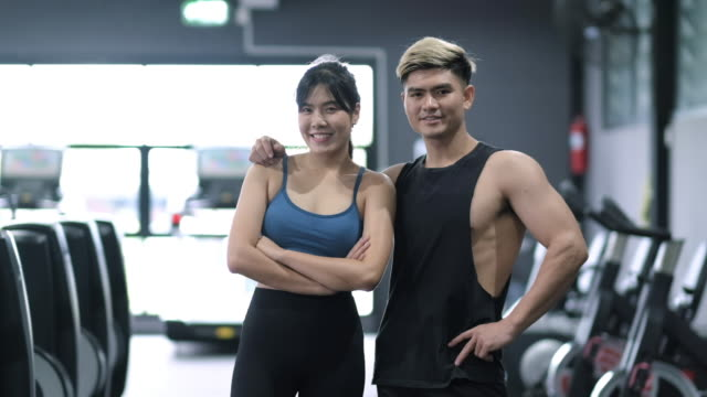 portrait young asian man and woman attractive fitness couples standing together after exercising in modern gym gym slow motion shot. - posizione corretta video stock e b–roll