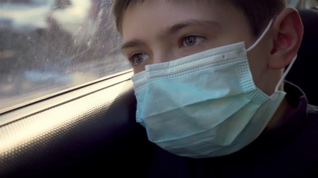 porträtt ung pojke i medicinsk mask tittar ut rörliga bilfönster på gatan. självisolering i karantän - face mask bildbanksvideor och videomaterial från bakom kulisserna