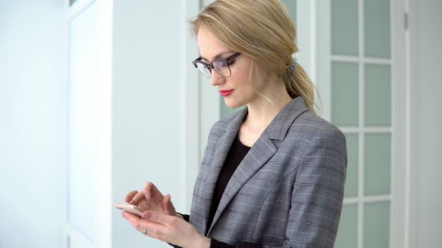vidéos et rushes de femme d'affaires jeune portrait à l'aide de smartphone tenant gadget mobile, message de sourire et envoyer des sms de fille. - mode bureau