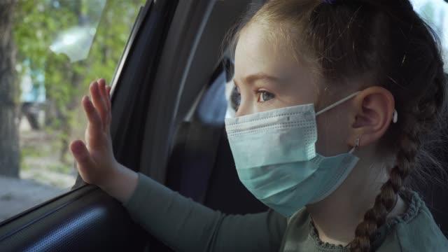 Porträtt ung flicka i medicinsk mask tittar ut flytta bilfönstret på gatan. Självisolering i karantän video