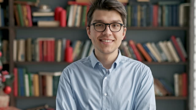 Portrait young man student smiling bookshelf library university