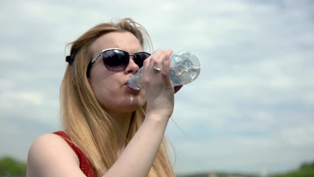 portrait young woman drinking cold water from a plastic bottle on hot summer day - femminilità video stock e b–roll