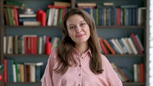 stockvideo's en b-roll-footage met portret jonge vrouw student glimlachende boekenplank bibliotheek universiteit - literatuur