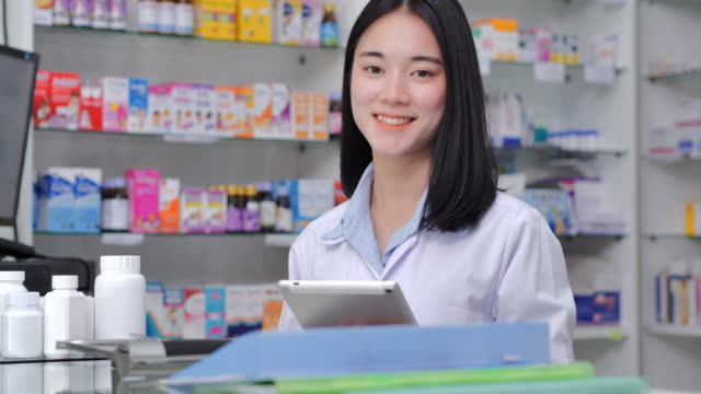 Portrait young women pharmacist smiling and holding tablet using for checking medication details on a box in pharmacy drugstore.Medicine,Healthcare,Medical education,Pharmaceutical sector,STEM,Innovation,Technology,Leadership,Expertise,Mentorship. - vídeo