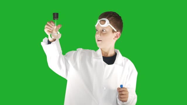 Portret van een school jongen chemicus een experiment uitvoeren in een kolf, op Chroma Key groen schermachtergrond video