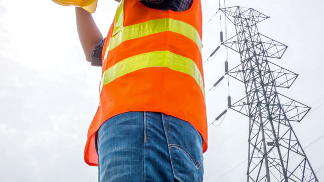 HD CRANE : Portraits electrical worker stand beside electric tower video