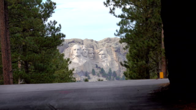 CLOSE UP ZOOM OUT: Portraits of famous Presidents carved into Mount Rushmore USA CLOSE UP ZOOM OUT: Iconic Mount Rushmore monument surrounded pine trees in Black Hills, South Dakota, United States. Famous US presidents Washington, Roosevelt, Jefferson and Lincoln rocky sculpture mount rushmore stock videos & royalty-free footage