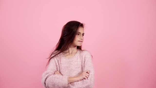 Portraity of pretty nice teen teenager have thought, looking around, searching for something. Copy space, clever touch chin hand fingers. Wears modern bright sweater. Isolated over pink background