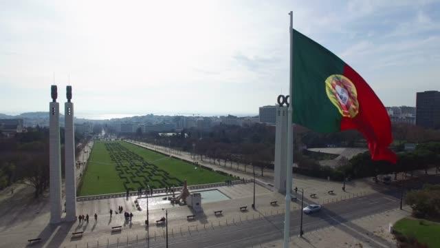 bandiera del portogallo sul parco eduardo vii, lisbona, portogallo - giardino pubblico giardino video stock e b–roll