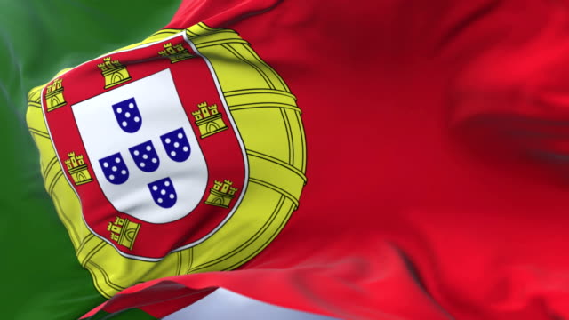 Portugal flag waving at wind in slow with blue sky, loop video