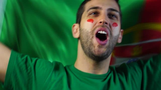 vídeos de stock, filmes e b-roll de português cara comemorando com a bandeira de portugal - futebol internacional